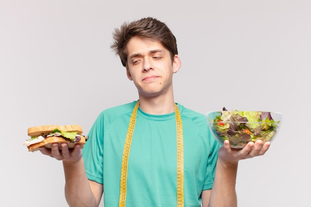 Młody mężczyzna na diecie i wątpiący lub niepewny wyraz twarzy