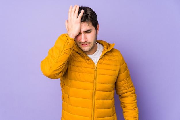Młody mężczyzna na fioletowej ścianie zapominający o czymś, uderzając dłonią w czoło i zamykając oczy.