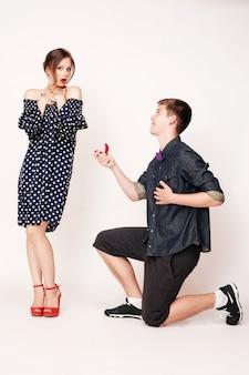 Młody mężczyzna na kolanach proponuje dziewczynie.