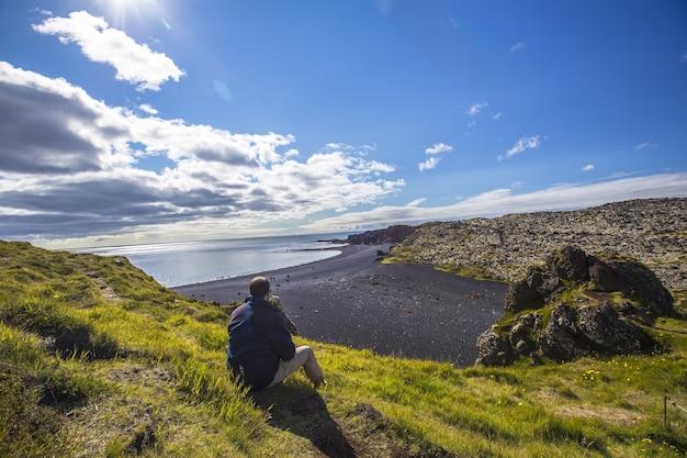 Młody mężczyzna na pięknych kamiennych plażach półwyspu snaefellsnes w naturalnym punkcie widokowym