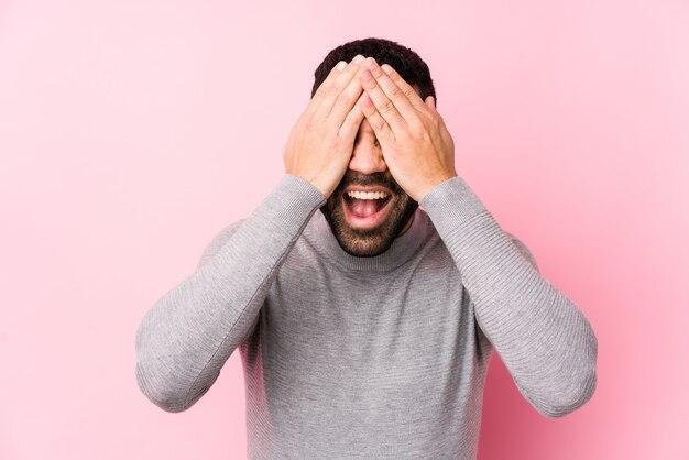 Młody mężczyzna na tle różowej ściany izoluje oczy dłońmi, uśmiecha się szeroko, czekając na niespodziankę