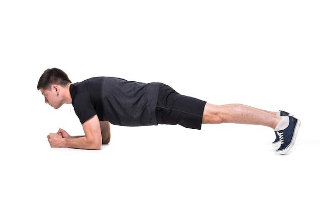 Młody mężczyzna na treningu brzucha podstawowa postawa deski na białym tle