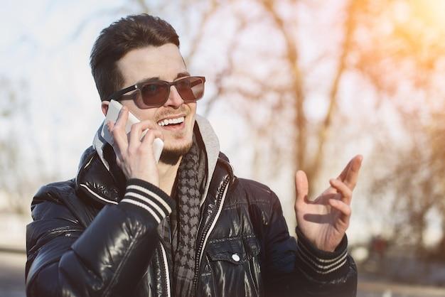 Młody mężczyzna na ulicy rozmawia przez telefon z uśmiechem