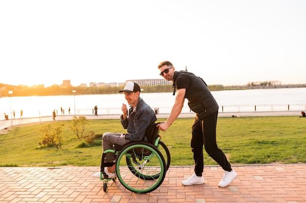 Młody mężczyzna na wózku inwalidzkim i jego przyjaciel spacerują na zewnątrz wysokiej jakości zdjęcia