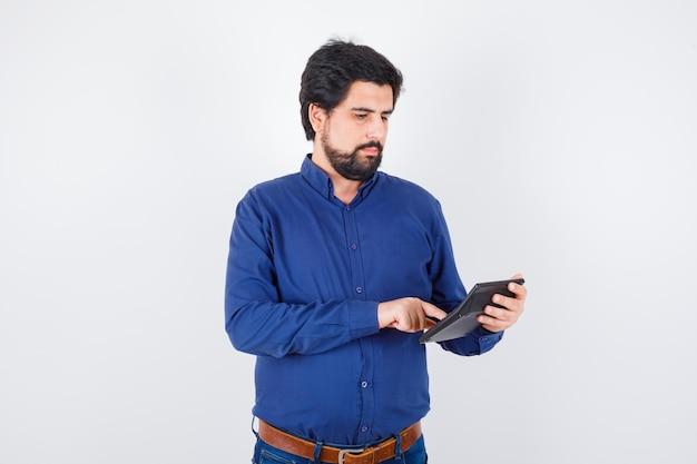 Młody mężczyzna naciskając przyciski kalkulatora w królewskiej niebieskiej koszuli i patrząc ostrożnie, widok z przodu.