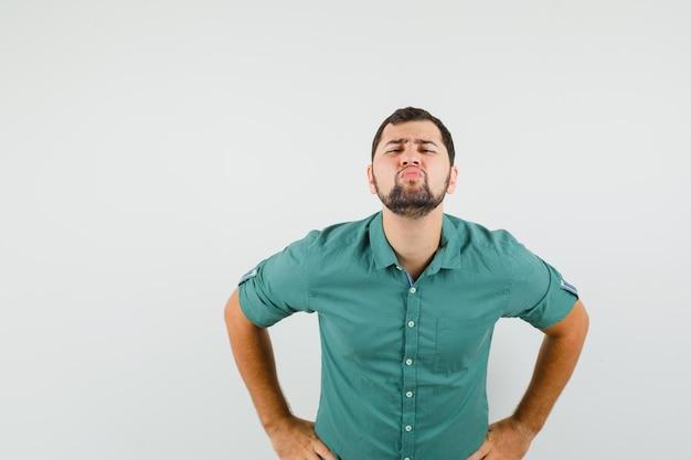 Młody mężczyzna nadyma usta w zielonej koszuli i wygląda dziwnie, widok z przodu.