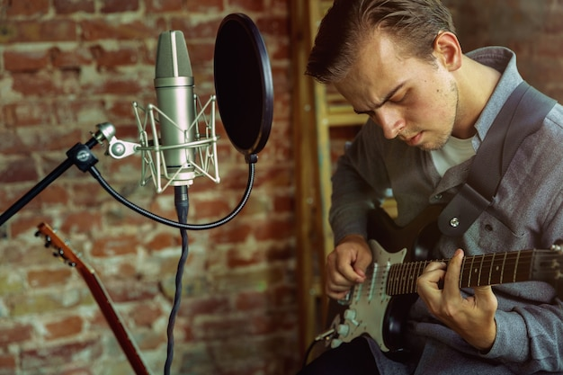 Młody mężczyzna nagrywa lekcję w domu na blogu z muzyką, gra na gitarze lub prowadzi internetowy tutorial, siedząc na poddaszu lub w domu. pojęcie hobby, muzyki, sztuki i twórczości.