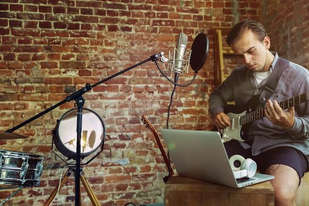 Młody mężczyzna nagrywa lekcję w domu na blogu z muzyką, gra na gitarze lub prowadzi internetowy tutorial, siedząc na poddaszu lub w domu