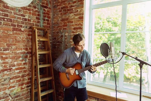 Młody mężczyzna nagrywa teledysk, lekcję lub piosenkę, gra na gitarze lub prowadzi internetowy tutorial, siedząc na poddaszu lub w domu
