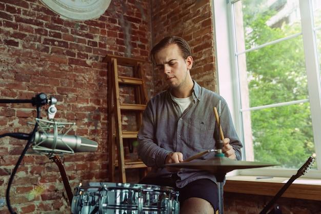 Młody mężczyzna nagrywa teledysk, lekcję w domu lub piosenkę, gra na perkusji lub prowadzi internetowy tutorial, siedząc na poddaszu lub w domu. pojęcie hobby, muzyki, sztuki i twórczości.