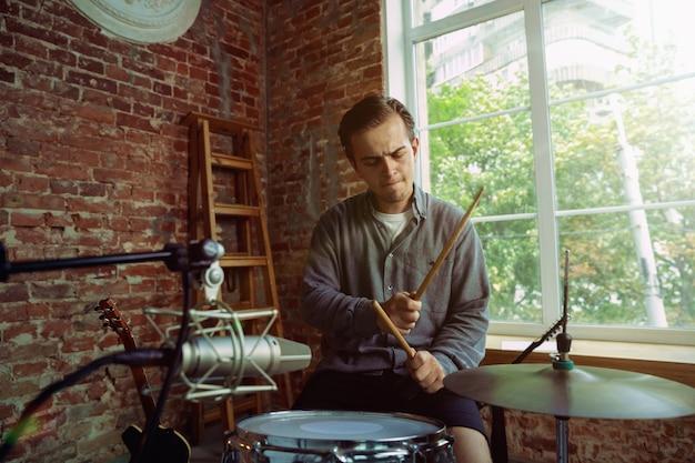 Młody mężczyzna nagrywa teledysk, lekcję w domu lub piosenkę, gra na perkusji lub prowadzi internetowy tutorial, siedząc na poddaszu lub w domu