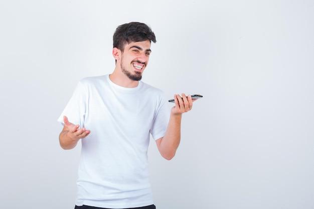 Młody mężczyzna nagrywający wiadomość głosową na telefonie komórkowym w koszulce i wyglądający błogo