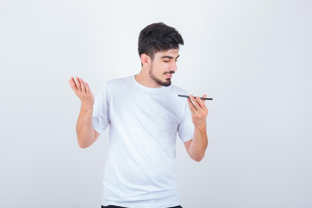 Młody mężczyzna nagrywający wiadomość głosową na telefonie komórkowym w koszulce i wyglądający pewnie
