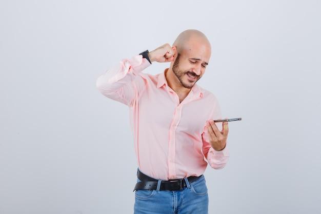 Młody mężczyzna nagrywający wiadomość głosową na telefonie komórkowym
