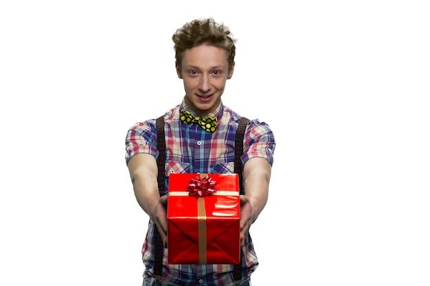 Młody mężczyzna nastolatek daje pudełko obiema rękami. na białym tle na białej ścianie.