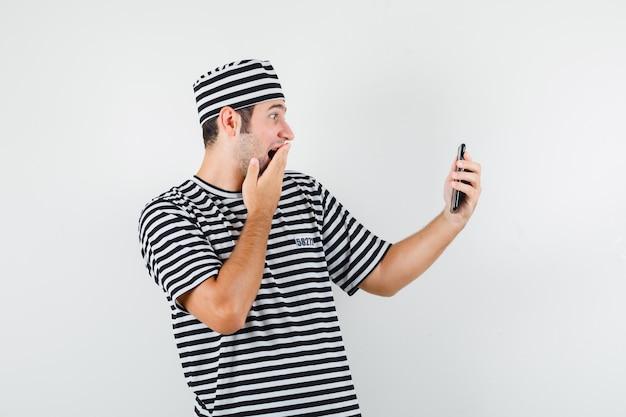 Młody mężczyzna nawiązywania połączenia wideo w t-shirt, kapelusz i patrząc zdumiony, widok z przodu.