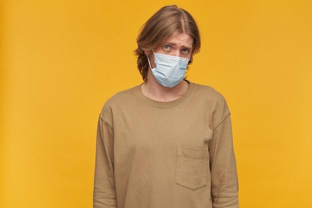 Młody mężczyzna, nieśmiały facet z blond włosami i brodą. noszenie beżowego swetra i medycznej maski ochronnej. przechyla głowę i patrzy smutno odizolowany na żółtej ścianie