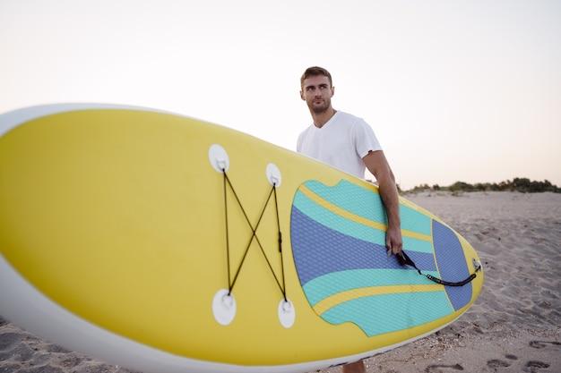 Młody mężczyzna niosący deskę sup po sesji surfowania po wodzie, z bliska
