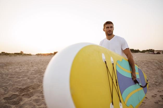 Młody mężczyzna niosący deskę sup po sesji surfowania po wodzie