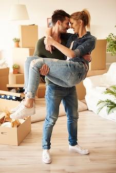 Młody mężczyzna niosący kobietę w ich nowym mieszkaniu