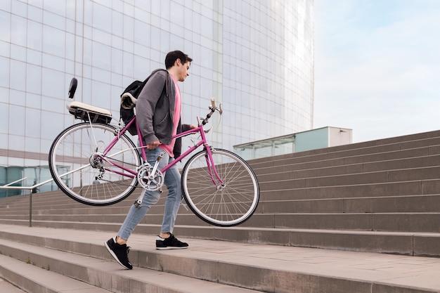 Młody mężczyzna niosący rower po schodach