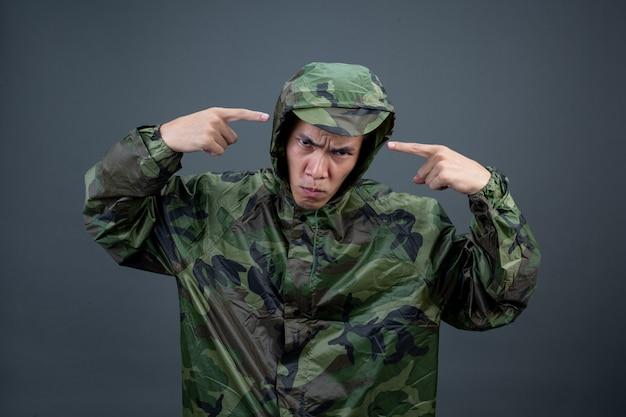Młody mężczyzna nosi kamuflażowy płaszcz przeciwdeszczowy i pokazuje różne gesty.
