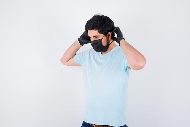 Młody mężczyzna nosi maskę medyczną i rękawiczki w koszulce i wygląda rozsądnie. przedni widok.