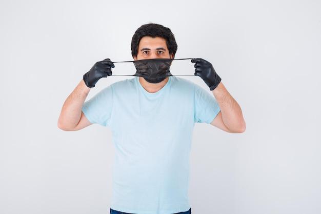 Młody mężczyzna nosi maskę medyczną w koszuli, dżinsach i rozsądnie wygląda. .