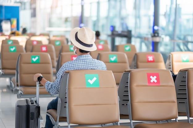 Młody mężczyzna nosi maskę na twarz siedzący na krześle w terminalu lotniska, ochrona przed zakażeniem koronawirusem (covid-19), podróżnik hipster gotowy do podróży. nowe koncepcje normalności i dystansu społecznego
