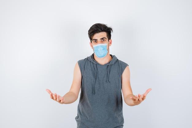 Młody mężczyzna nosi maskę, rozciągając ręce, trzymając coś w szarej koszulce i patrząc poważnie