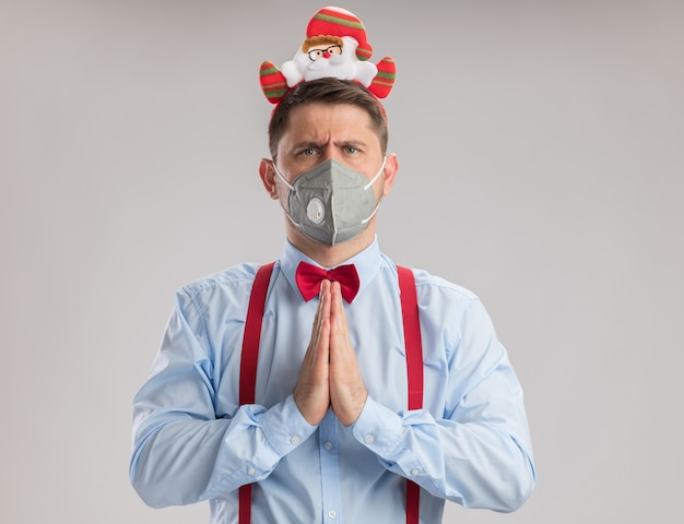 Młody mężczyzna nosi muszkę na szelkach w obręczy ze świętym mikołajem w ochronnej masce na twarz, patrząc na kamerę z poważną twarzą trzymającą się za ręce, jak modląca się, stojąc na białym tle
