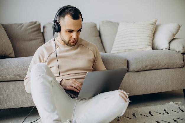 Młody mężczyzna nosi słuchawki i korzysta z komputera w domu