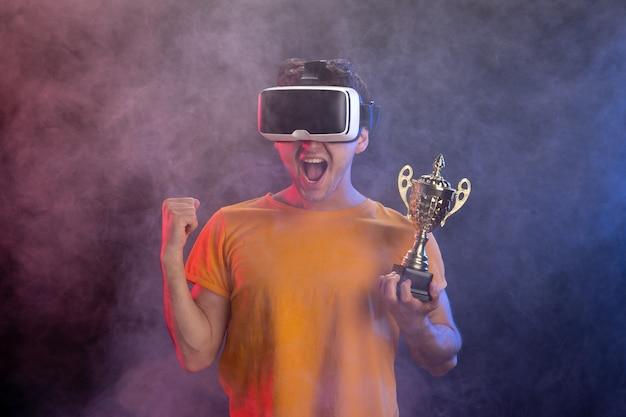 Młody mężczyzna nosi zestaw słuchawkowy wirtualnej rzeczywistości na ciemnej powierzchni