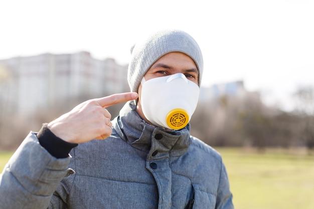 Młody mężczyzna noszący maskę chroniącą przed grypą lub infekcjami