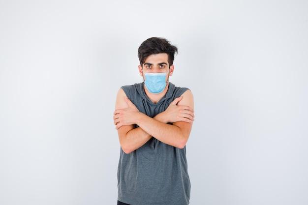 Młody mężczyzna noszący maskę, drżący z zimna w szarym t-shircie i patrzący poważnie