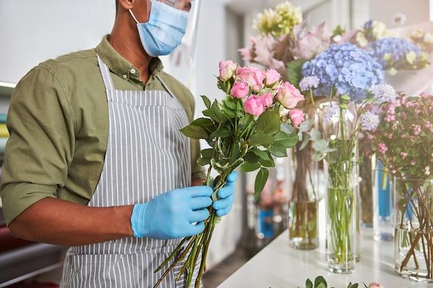 Młody mężczyzna noszący maskę i szkło ochronne w kwiaciarni podczas robienia bukietów