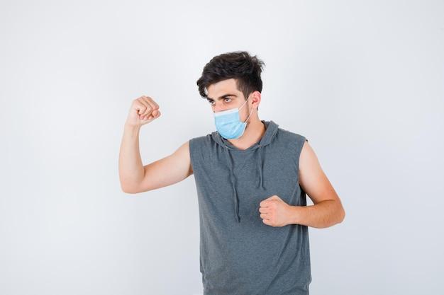 Młody mężczyzna noszący maskę, pokazujący mięśnie i zaciskającą pięść w szarym t-shircie i wyglądający poważnie