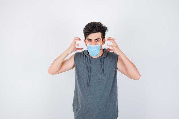 Młody mężczyzna noszący maskę, trzymający ręce w pobliżu twarzy w szarej koszulce i patrzący poważnie and