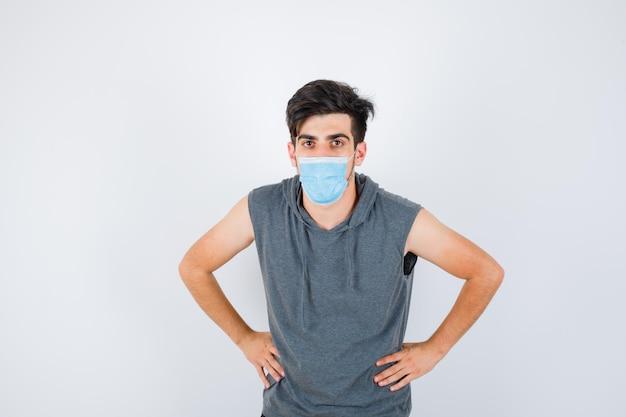 Młody mężczyzna noszący maskę, trzymający ręce w talii w szarym t-shircie i wyglądający poważnie