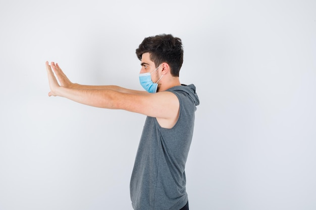 Młody mężczyzna noszący maskę, wyciągający ręce w lewo w szarym t-shircie i wyglądający poważnie