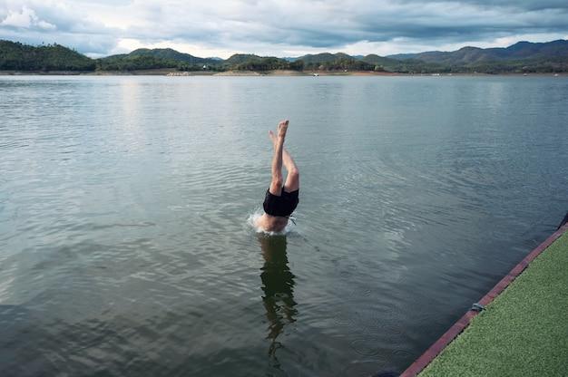 Młody mężczyzna nurkujący w jeziorze w parku narodowym