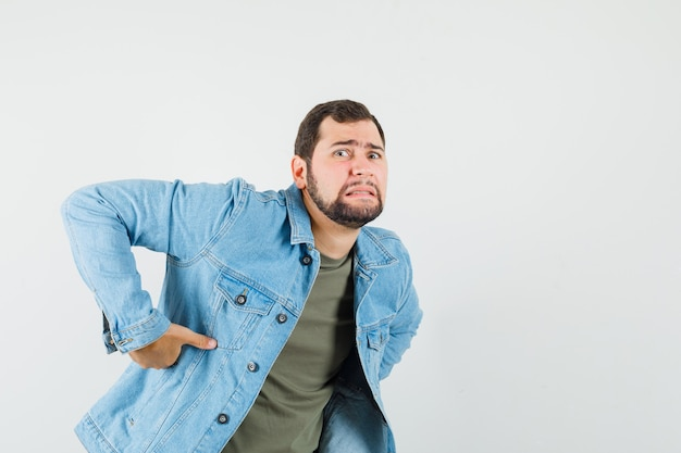 Młody mężczyzna o bolesnym bólu pleców w t-shirt kurtce i wyglądający na zmęczonego