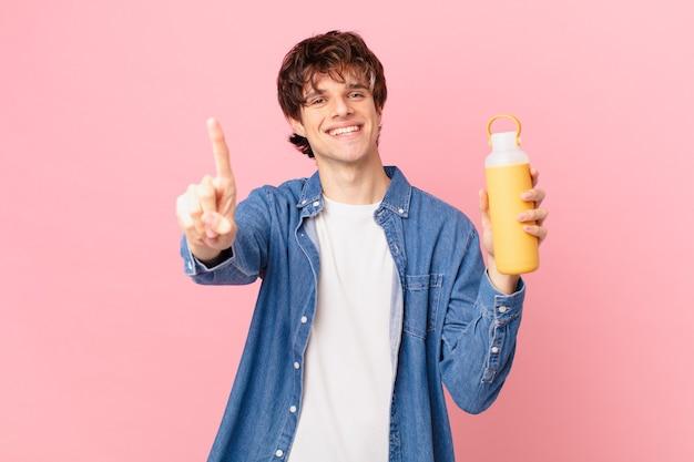 Młody mężczyzna o gładkim uśmiechu i przyjaznym wyglądzie, pokazujący numer jeden