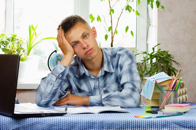 Młody mężczyzna o niebieskich oczach, ubrany w kraciastą koszulę, siedzi zaskoczony w swoim miejscu pracy. koncepcja edukacji.