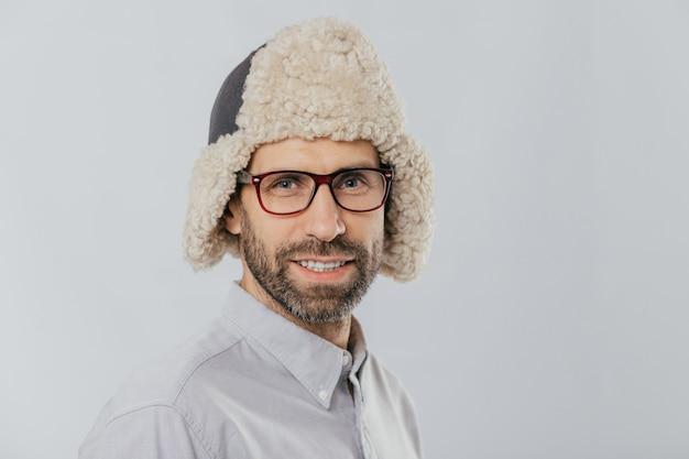 Młody mężczyzna o przyjemnym wyglądzie, nosi ciepły futrzany kapelusz, przezroczyste okulary, modele na białej ścianie studia
