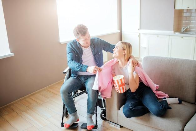 Młody mężczyzna o specjalnych potrzebach opiekuje się dziewczyną. siedzi na wózku inwalidzkim i rozkłada koc na ramionach. osoba ze specjalnymi potrzebami. uśmiecha się do siebie.