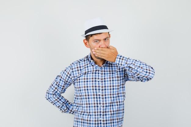 Młody mężczyzna obejmujące usta ręką w kraciastej koszuli