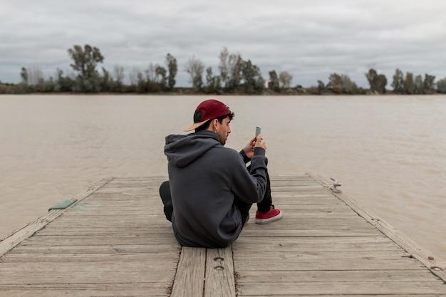 Młody mężczyzna od tyłu ubrany w szary sweter i czerwoną czapkę za pomocą smartfona i robiąc zdjęcia, siedząc na molo nad rzeką w pochmurny dzień