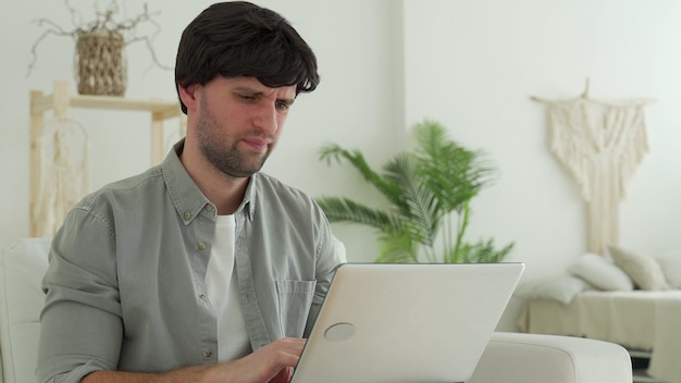 Młody mężczyzna odbiera bardzo złe wieści na ekranie swojego laptopa, zdenerwowany i sfrustrowany awarią.