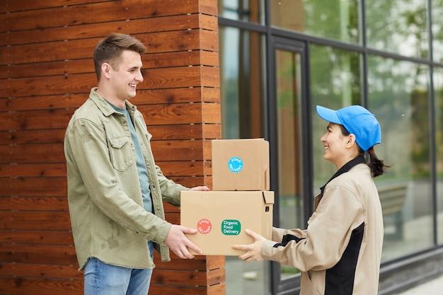 Młody mężczyzna odbiera paczki od kuriera, gdy stoją na zewnątrz